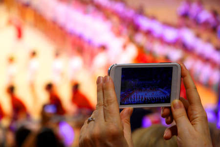 incorporates: womans hand with new smartphone that incorporates a show in a stadium