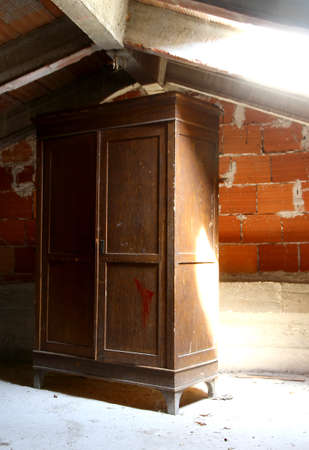 abandonment: emblematic antique wardrobe in a dusty attic of a nursery