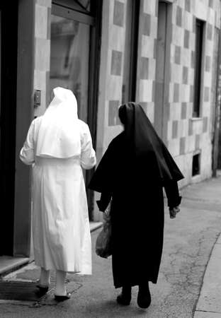 catholic nuns: two nuns with black suit and white dress walking a alongside each other for the city