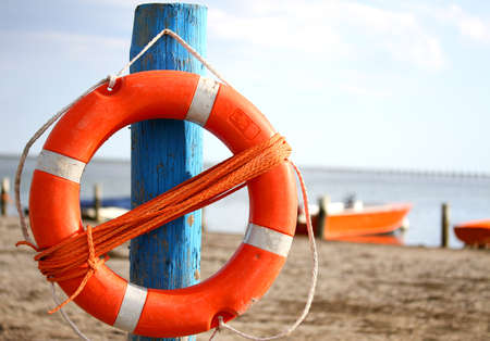 lifejacket: pole with orange lifejacket at sea on the beach by the sea Stock Photo