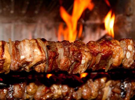 pollo rostizado: escupir asado con carne sabrosa cocinada en un asador en la chimenea Foto de archivo