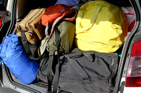 duffle: suitcases and travel bags in the trunk of the car before leaving for summer vacation Stock Photo