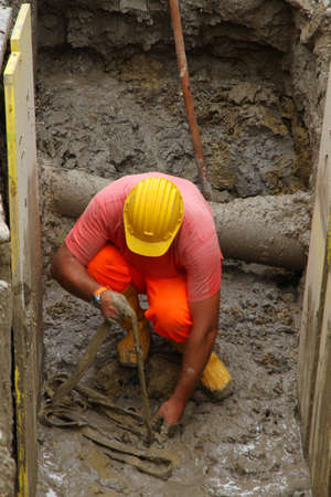 roadwork: construction worker in the excavation of a roadworks for the laying of optical fibre