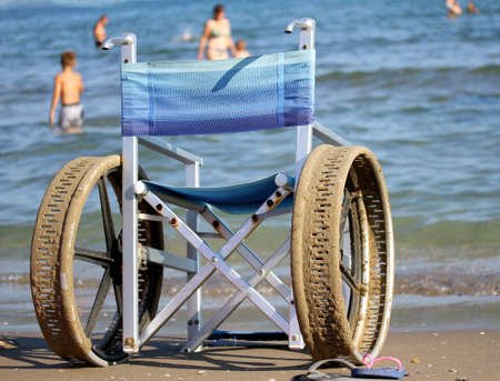 Special wheelchair with perforated wheels for swimming in the sea of people with disabilities photo