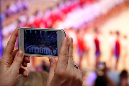 old woman's hand with smartphone that takes up a show in a stadium Zdjęcie Seryjne