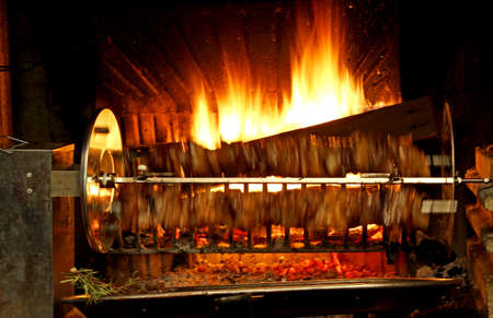 pollo rostizado: fuego encendido en la chimenea y el asador que corre muy rápido con la carne Foto de archivo