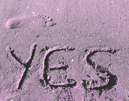 great written YES engraved on the sand of the Sea Beach and a foot footprint photo