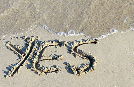 sea wave clears the word YES on the sand of the Sea Beach 2 photo