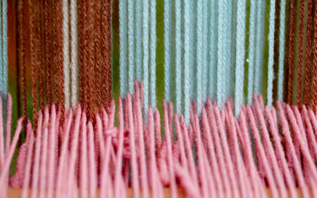 ancient woolen threads woven into the loom to make the fabrics photo
