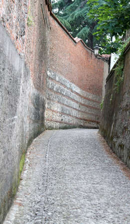 cobblestone lane with bounded by high walls of brick photo