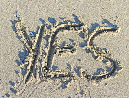 huge written YES on the sand of the Sea Beach near the sea photo