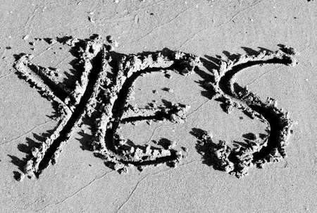 huge written YES designed on the sand of the beach in black and white photo