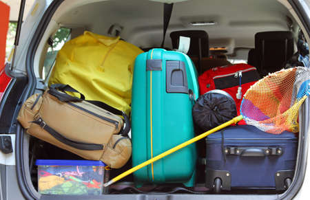 duffle bag and trolley with a fishing net in the trunk of the car departing photo