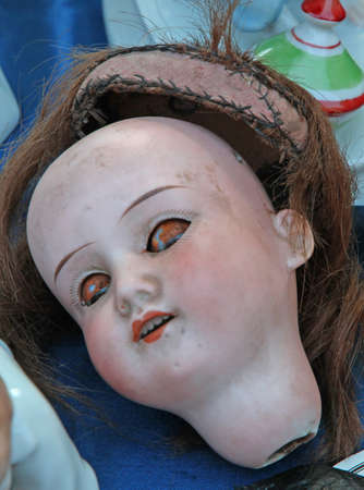 beheading: very scary doll face in an antique shop