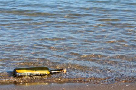 secret message in glass bottle in the ocean photo