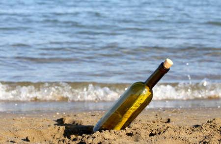 castaway: secret message in glass bottle on the seashore