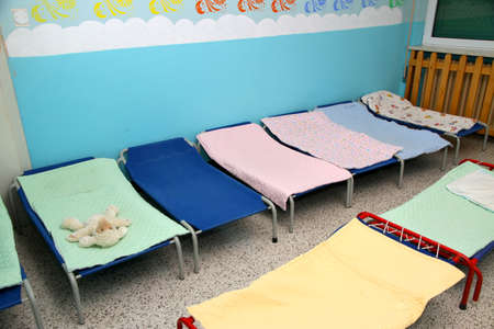dormitory: Rollaway beds and cots in brightly colored dormitory of a nursery Stock Photo