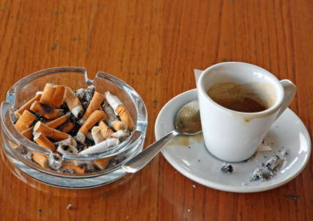 chock: ashtray chock full of cigarette butts and a cup of coffee Stock Photo