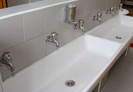 sinks: sinks and washbasins with very low taps in the toilets of a nursery Stock Photo