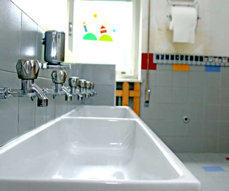 sinks and washbasins with very low taps in the toilets of a nursery photo