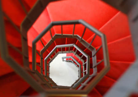 giddy steep spiral staircase with red carpet photo