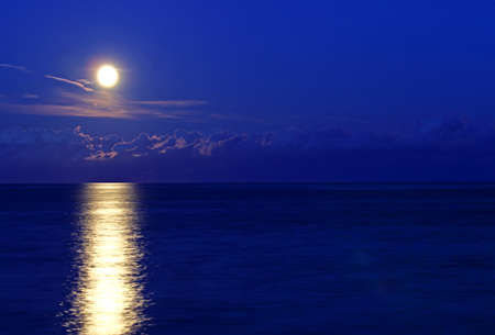 incredible full moon reflected in the sea at dusk