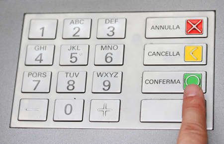 confirms: index that confirms the secret code in the keyboard of an italian ATM to withdraw cash Stock Photo