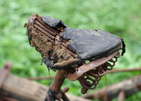 Rusty bike saddle, completely destroyed of the last century