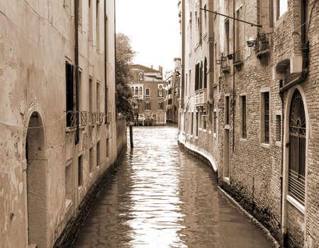 narrow navigable canal in Venice in VENETO Italy sepia