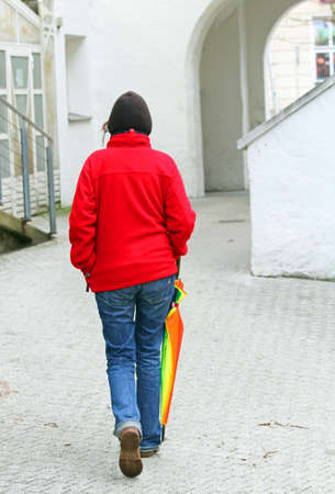 woman in blue jeans with red Sweatshirt walks with colored umbrella in the city photo