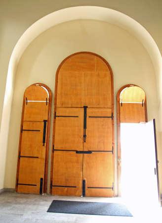 great church door with light entering from an open door Stock Photo
