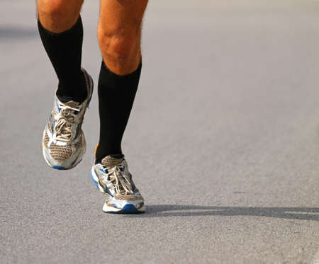 get tired: very fast runner with sneakers during the Marathon on paved road