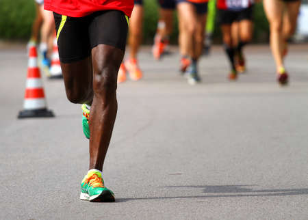frenetic: fast athlete runs down the street during the race outdoors Stock Photo