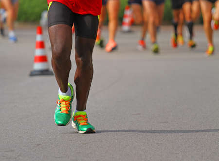 frenetic: athlete runs down the street during the race outdoors with other people