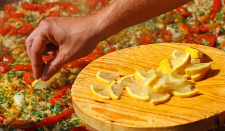 Cook puts yellow lemon slices in the paella with seafood and peas photo