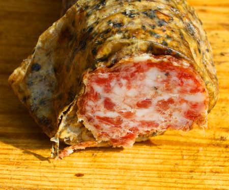 salame: wild boar salami on a wooden cutting board in Tuscany
