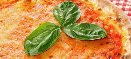 three Basil leaves over the delicious Italian pizza in a pizzeria in Naples photo