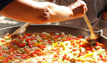 adds: Cook adds a ladleful of broth to the paella valenciana