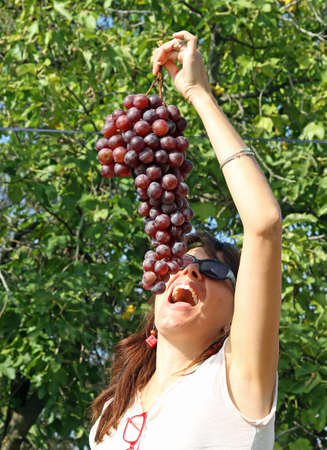 beautiful woman eat a huge bunch of grapes in autumn photo