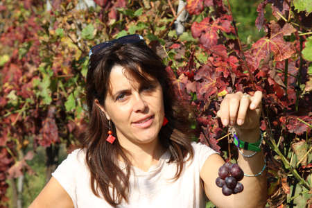 nice woman smiling with a little bunch of grapes in autumn photo