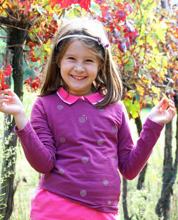 pretty little girl smiling in the vineyard in autumn photo