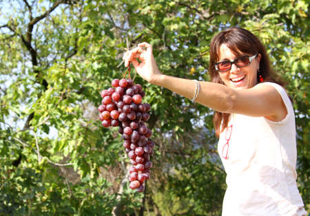 very beautiful woman smiling with grapes on hand photo