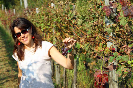 pretty woman with a little bunch of grapes in autumn photo