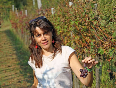 nice woman with a little bunch of grapes in autumn photo
