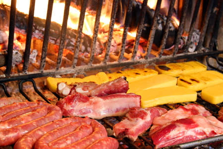 beef and pork cooked on the grill in the glowing embers of the fireplace photo