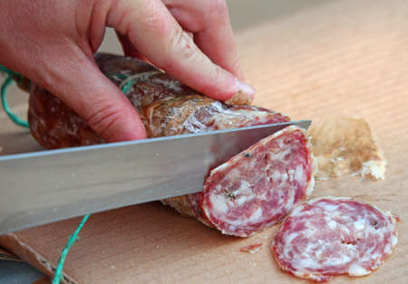 cut: Cooks hand slicing the salami with a knife-sharp