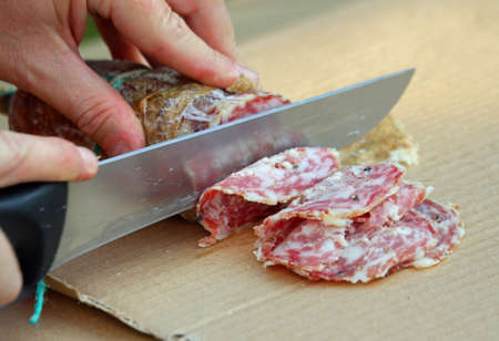 Cook cut the genuine salami with a knife Stok Fotoğraf