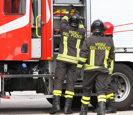 イタリアの消防士が緊急事態を処理するとき消防車の近くで作業