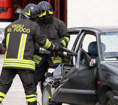 accidente laboral: bomberos abren la puerta del coche con un potente tijeras neum�ticas Foto de archivo
