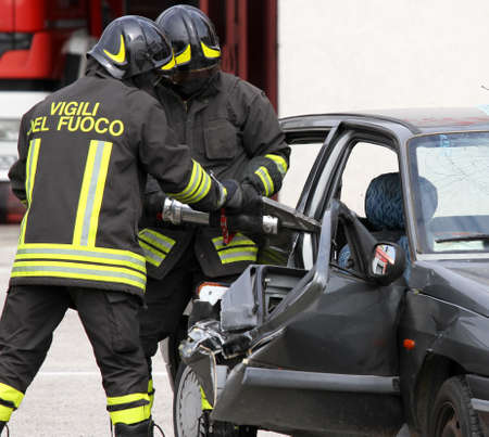 fire car: firemen open the door of the car with a powerful pneumatic shears